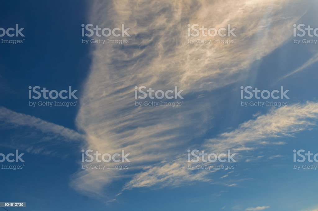 Sparse clouds in the blue sky morning background. Fluffy clouds in the blue sky evening background. Blue sky in summer background with tiny clouds, stock photo