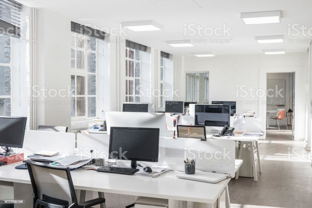 Sparse office with white desks and computer monitors stock photo