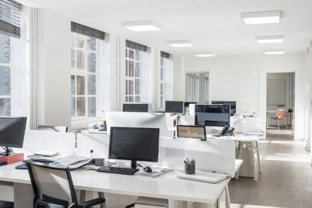 白い机とコンピューターのモニターでまばらなオフィス ストックフォト