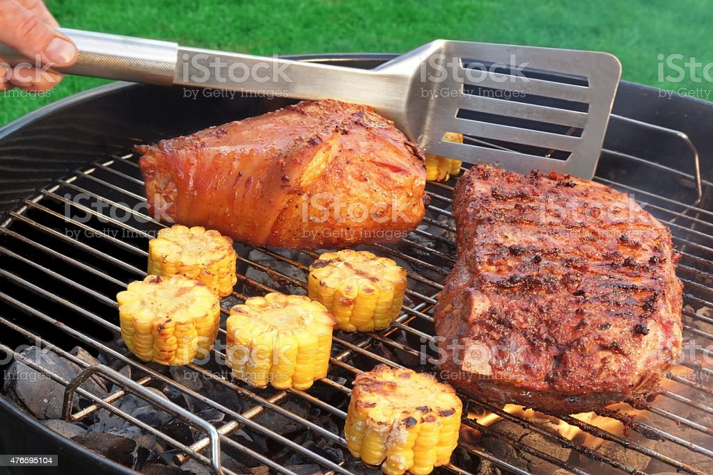 Spatula, BBQ Pork Knuckle and  Spareribs On The Flaming Grill stock photo