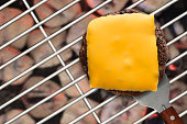 Spatula removes a grilled cheese burger from a glowing grill with charcoal briquettes