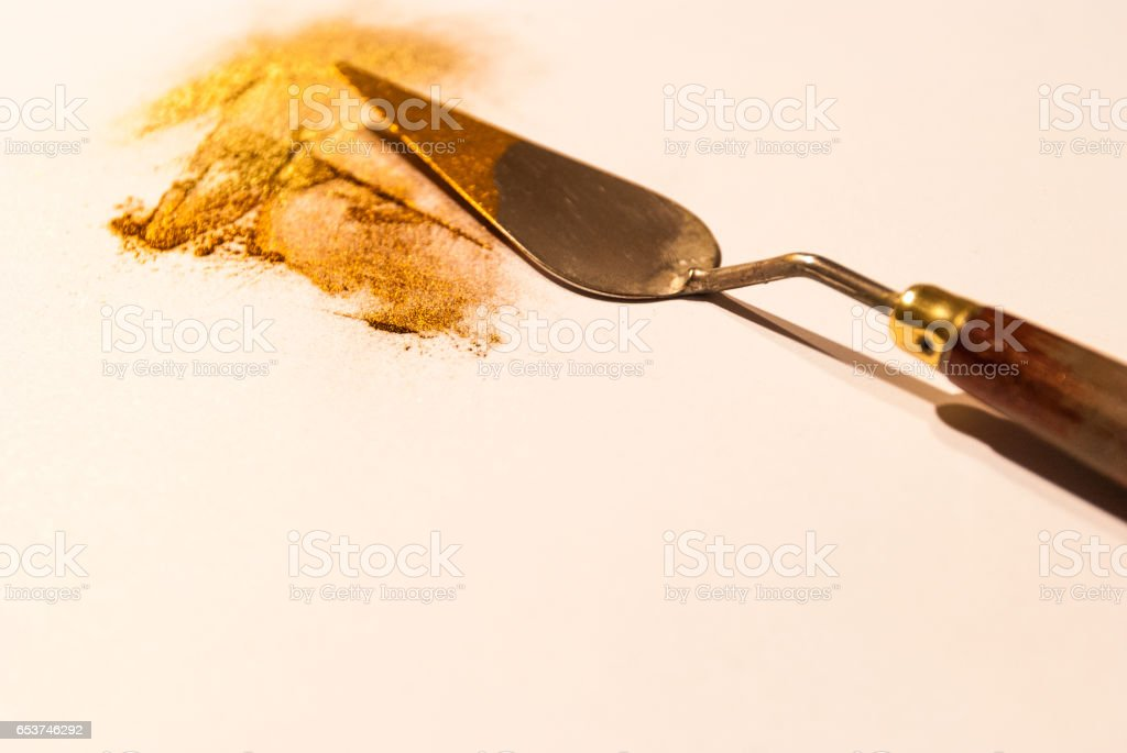 Spatula with golden and orange powder pigments on a white sheet stock photo