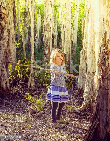 Child, little girl, carries a huge walking stick in a rural, woodsy forest.