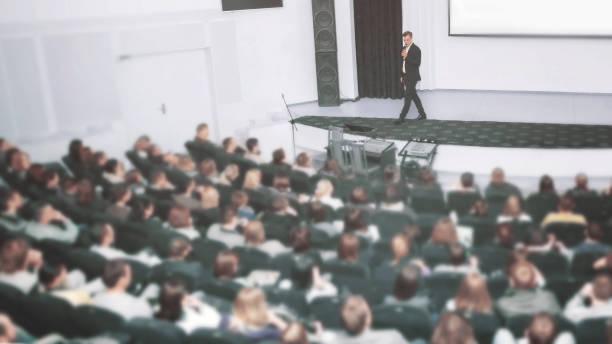 Alto-falante em uma Convenção de negócios e apresentações. A audiência sobre o grande número de pessoas - foto de acervo