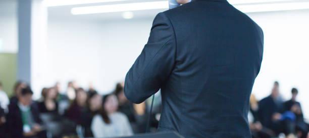 カンファレンスで講演者が企業ビジネスについて講演。プレゼンターがプレゼンテーションを行うホールの聴衆。ビジネスワークショップで企業幹部による講演会を開催。 - 芸能・娯楽施設 ストックフォトと画像