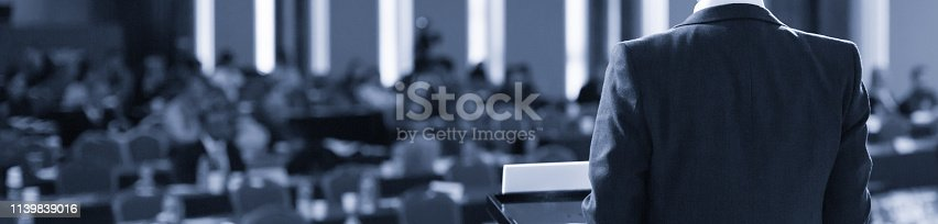 istock Speaker at Conference Stage. Executive Business Entrepreneur at Seminar Photo. Business Presentation Presenter Speech at Meeting. Corporate Forum Event for Investor Audience. Black and White 1139839016