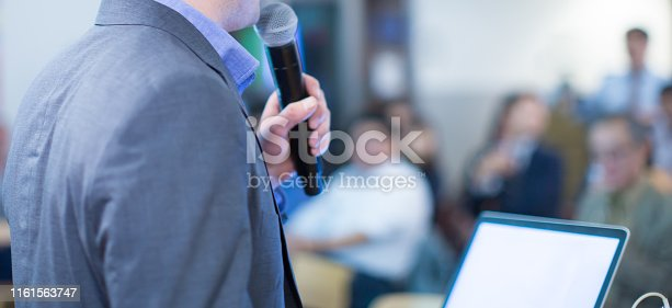 istock Speaker giving a talk at a corporate business conference. Audience in hall with presenter in front of presentation screen. Corporate executive giving speech during business and entrepreneur seminar. 1161563747