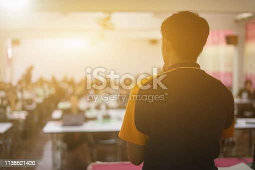 istock Speaker giving a talk on corporate Business Conference. Audience at the meeting room hall or seminar room with attendee background. Businessman and Entrepreneurship event.vintage color selective focus 1138521420