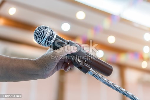 508658652istockphoto Speaker holding microphone for speak, presentation on stage in public conference seminar room. Business meeting and education in teaching classroom concept. Event light convention hall Background 1132264103