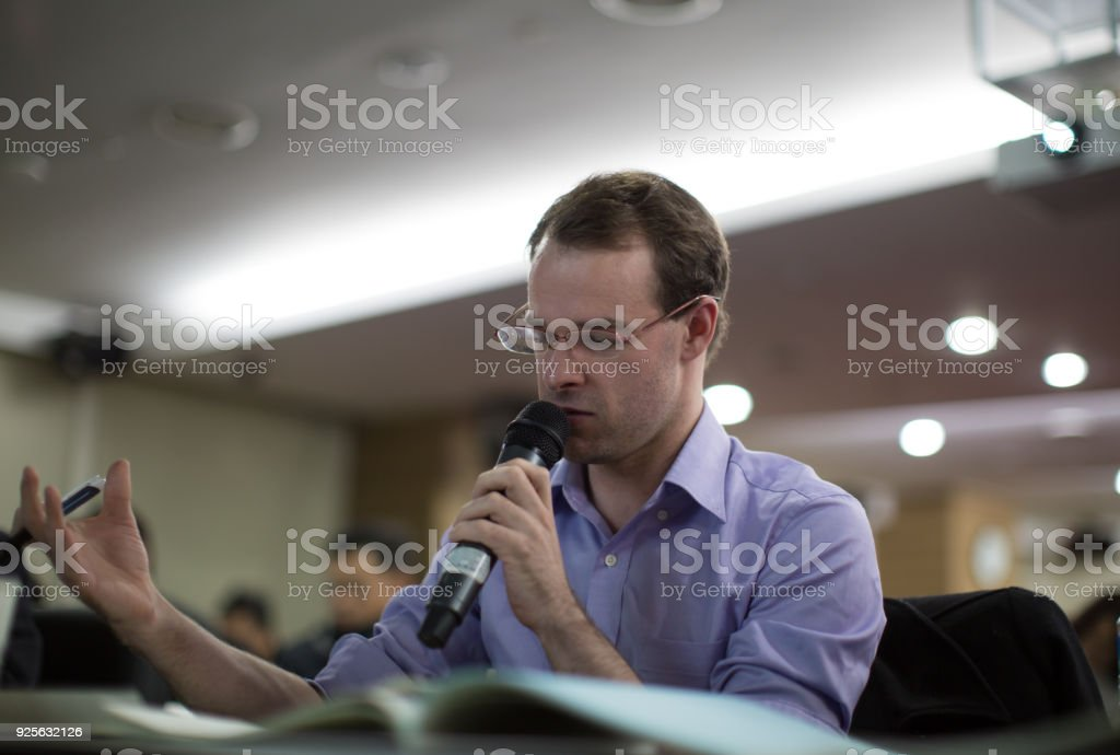 A Speaker is Speaking into Microphone with Notebook in Front in a Room with People. stock photo