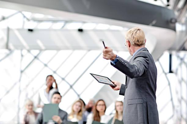 Speaker presenting at business seminar stock photo