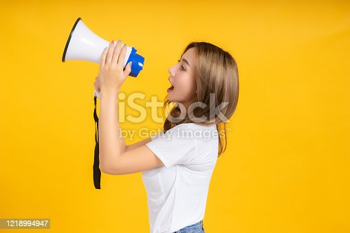 690508154 istock photo Speaking Loud noise announce of young asian woman with megaphone promotional advertising in white t-shirt smiling emotion on yellow background isolated studio shot with copy space. 1218994947