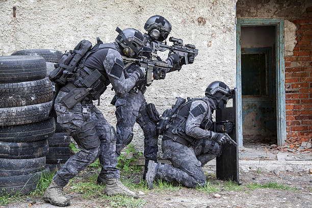 Spec ops police officer SWAT Spec ops police officers SWAT in black uniform in action counter terrorism stock pictures, royalty-free photos & images