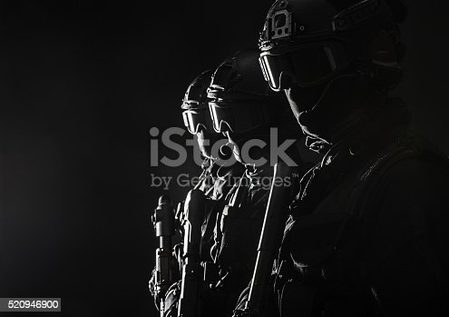 Spec ops police officers SWAT in black uniform and face mask studio shot