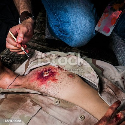 Special effects makeup artist creating a gunshot wound to the chest of a military soldier.
