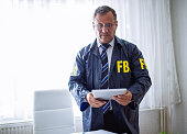 FBI agent, man working in the office on a crime. He is working on digital tablet.