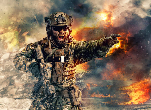 special forces in action Bearded soldier of special forces in action pointing target and giving attack direction. Burnt ruins, Heavy explosions, gunfire and smoke billowing on background battlefield stock pictures, royalty-free photos & images
