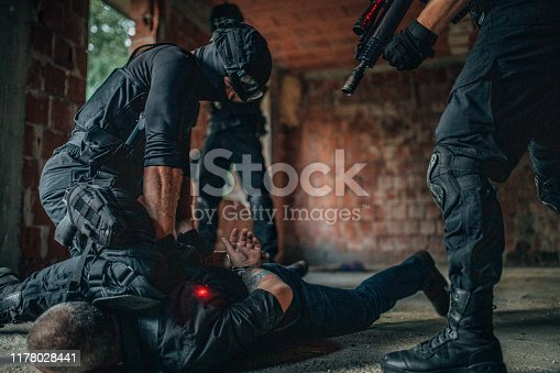 Group of man, special police forces in abandoned house, making an arrest on a criminal.