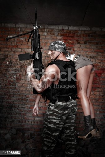 Armed man in protactive cask with light machinegun on the ruined building backround.