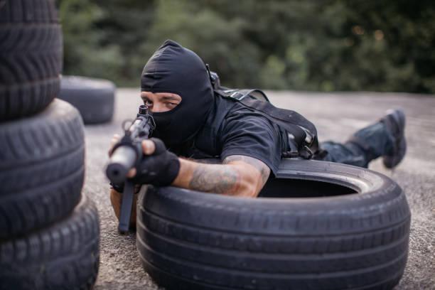 spezialeinheiten polizei kerl zeigt eine gewehr - wächter tattoo stock-fotos und bilder