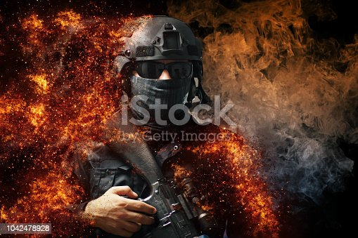 Special forces soldier with rifle in the fire and smoke