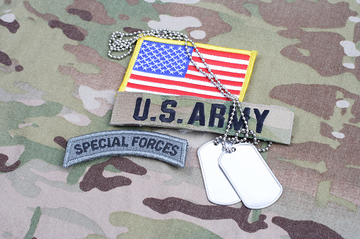 istock US ARMY special forces tab, flag patch, with dog tag on camouflage uniform 1190926161