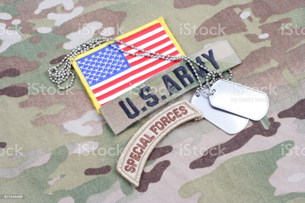 US ARMY special forces tab, flag patch, with dog tag on camouflage uniform stock photo