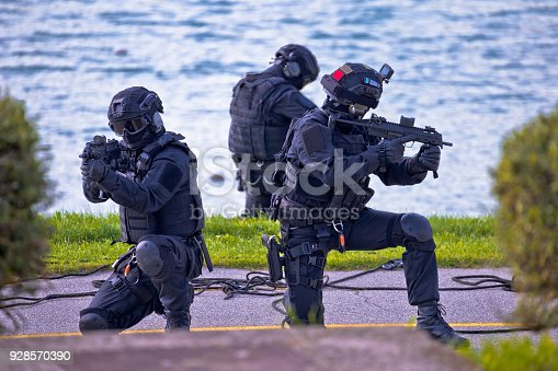 istock Special forces tactical team of three in action, unmarked and unrecognizable swat team 928570390