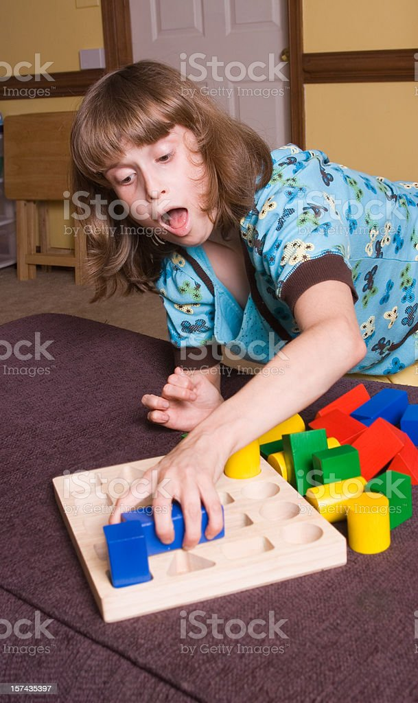 Special little girl playing with blocks stock photo