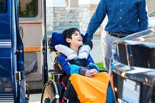 Special needs boy in wheelchair on vehicle handicap lift