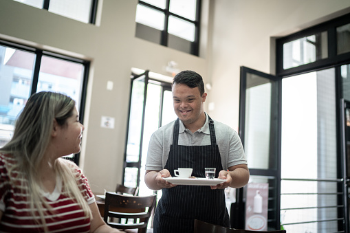 Special needs waiter serving coffee to customer in a coffee shop