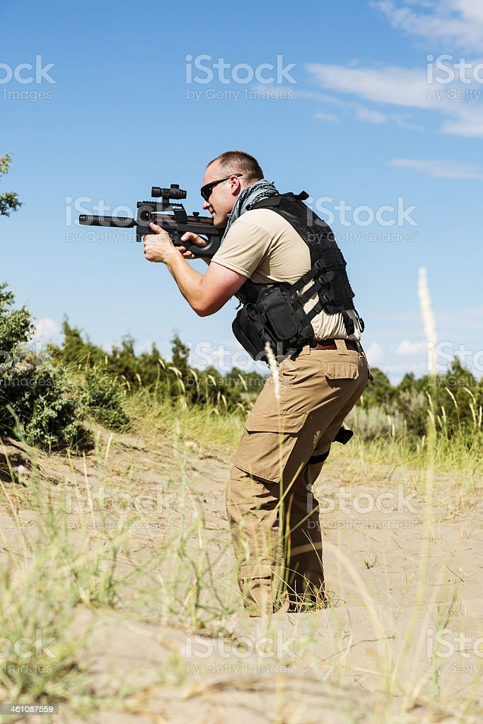 Special Operations soldier taking aim on patrol in desert landscape stock photo