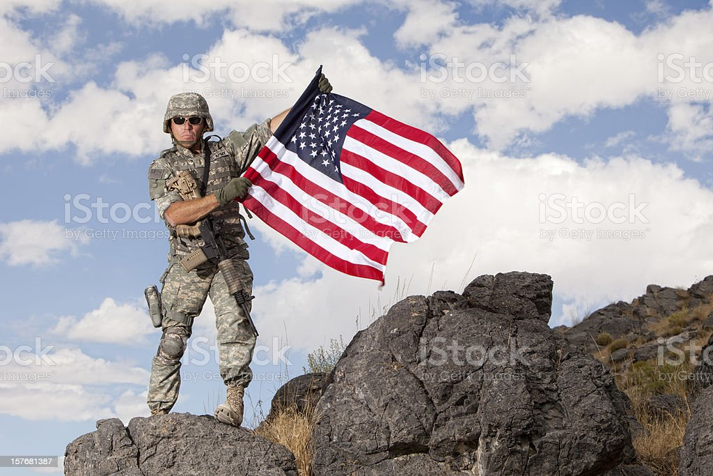 Special ops military soldier holding an american flag stock photo