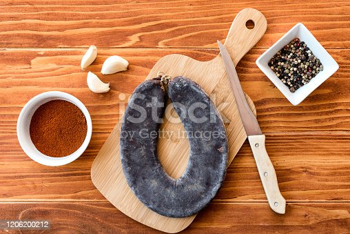Special Pirot horseshoe ironed sausage - Peglana Pirotska kobasica, made from veal, sheep and goat   meat, with addition of garlic, mixed pepper, powdered chili peppers and spices, on a cutting board and wooden table