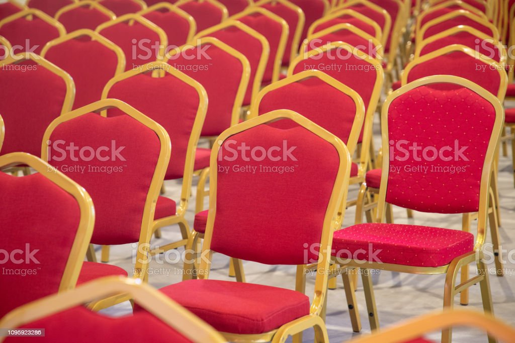 Special seat standing out in a row of red chairs in auditiorium