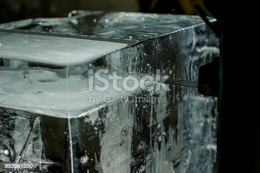 Special tool cutting the big clear ice cube on the ice production plant in the dark