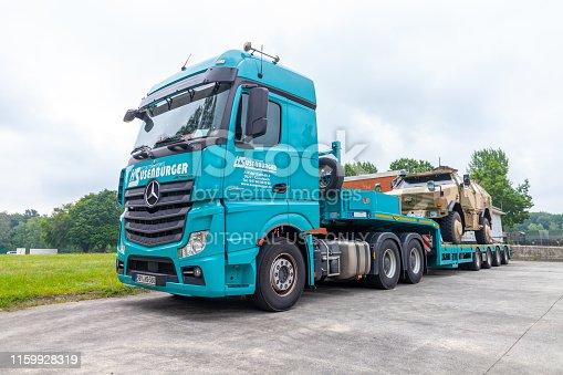 istock Special transport truck from Susenburger with a KMW Dingo on the trailer stands on a street 1159928319
