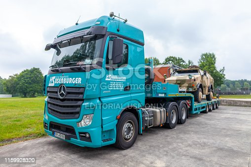 istock Special transport truck from Susenburger with a KMW Dingo on the trailer stands on a street 1159928320