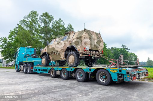 istock Special transport truck from Susenburger with a KMW Dingo on the trailer stands on a street 1159928321