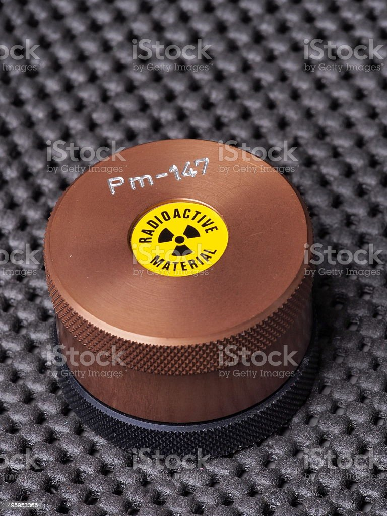 Specialist container with warning sticker containing radioactive isotope Promethium stock photo