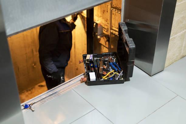 specialist fixing or adjusting lift mechanism in elevator schaft. regular repair, service and maintenance of elevator - ascensore foto e immagini stock