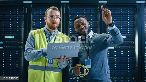 1131198396istockphoto IT Specialist in Glasses and High Visibility Vest with Laptop Computer and Black Technician Colleague Talking in Data Center while Standing Next to Server Racks. Running Diagnostics and Looking Up. 1131198051