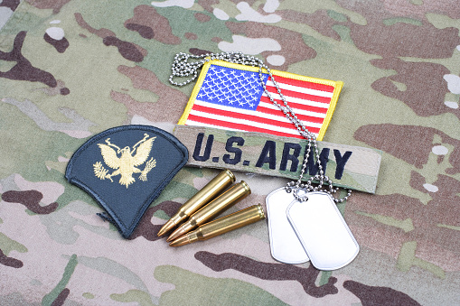 istock US ARMY Specialist rank patch, flag patch, with dog tag and 5.56 mm rounds on camouflage uniform 1190926214