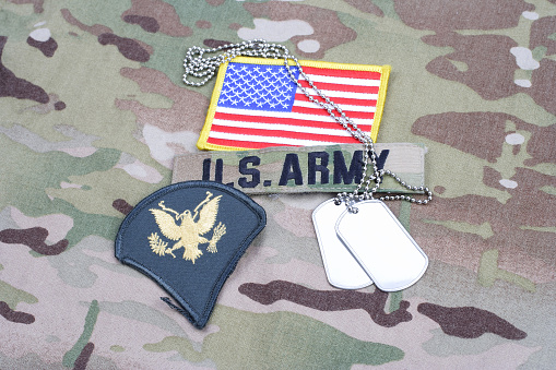 istock US ARMY Specialist rank patch, flag patch, with dog tag on camouflage uniform 1190926221