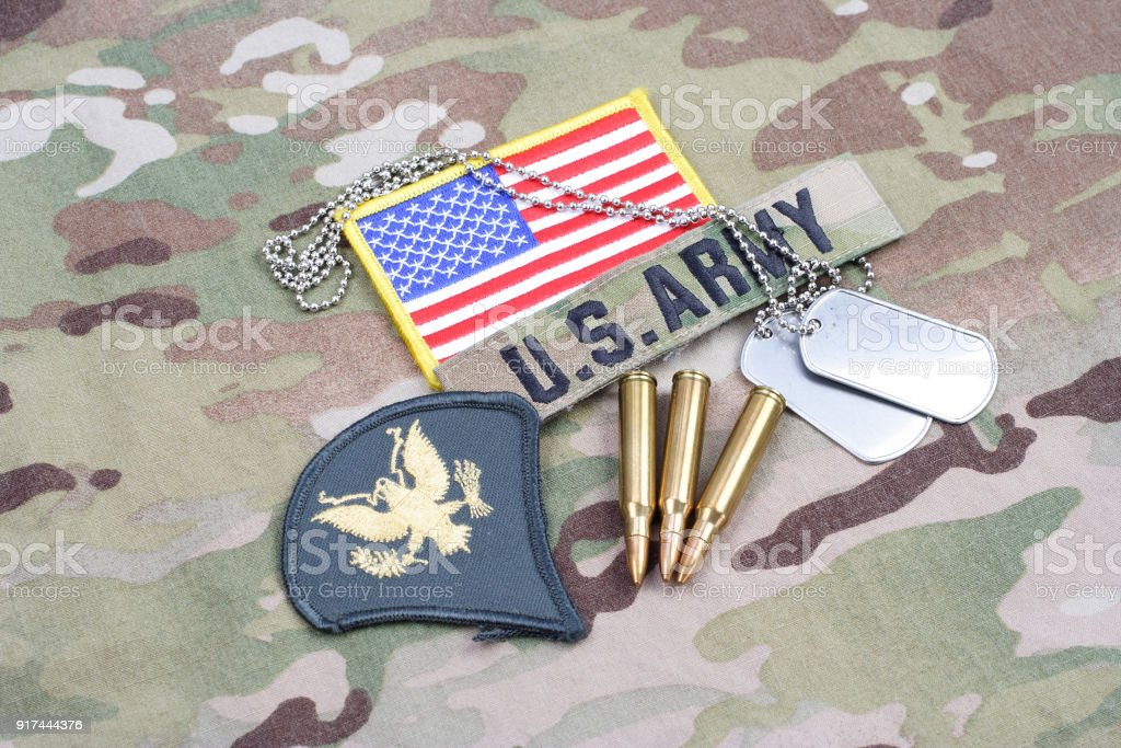 US ARMY Specialist rank patch, flag patch, with dog tag with 5.56 mm rounds on camouflage uniform stock photo
