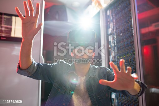 istock IT specialist using virtual reality goggles in server room 1153742609