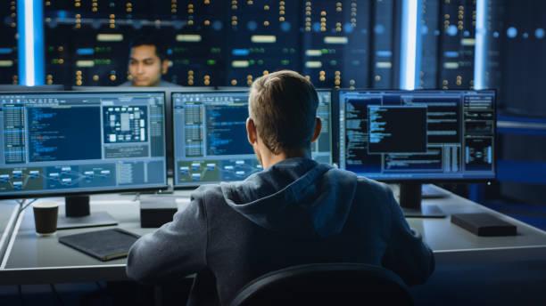 IT-Spezialist arbeitet auf Personal Computer mit Bildschirmen, die Software-Programm mit Coding Language Interface zeigen. Im Hintergrund Technical Room des Rechenzentrums mit professioneller Arbeit – Foto