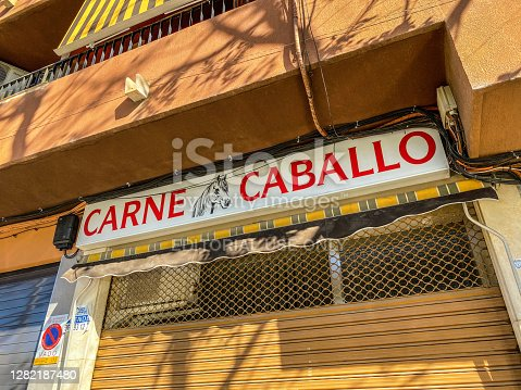 Valencia, Spain - October 23, 2020: Low angle view of commercial sign for butchery selling horse meat. This type is considered a specialty not sold by everyone dedicated to the meat business