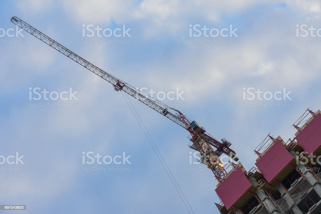 Specially diagonal image of construction tower crane next to building under construction against the background of the blue sky. Unusual foreshortening. Copy space stock photo