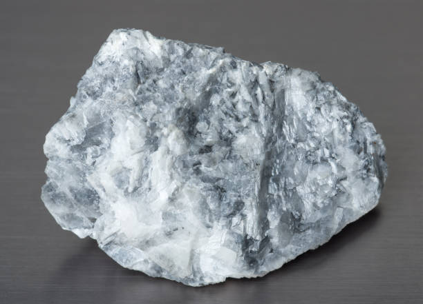 specimen of mineral magnesite on gray background - magnesium stock photos and pictures